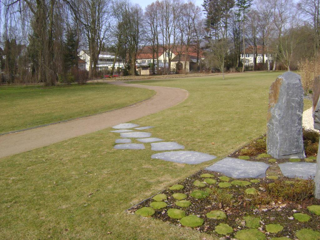 """Bad Pyrmont, Kurpark - Polygonale Wegeplatten """"gespalten"""", Stele"""